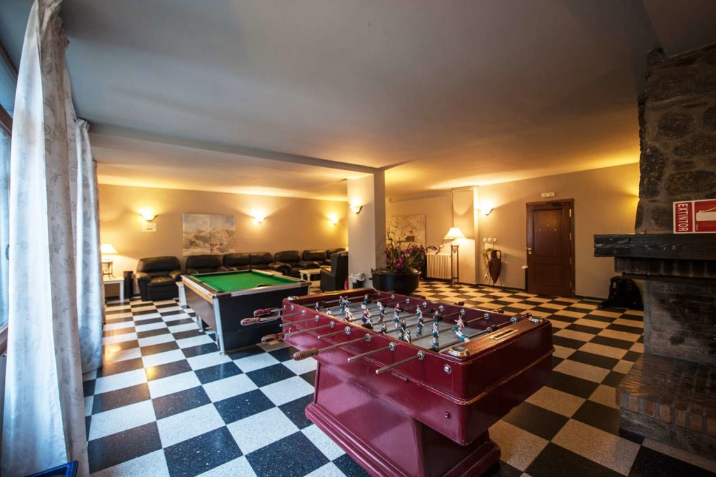 A warm atmosphere in the mountains: a fireplace and a pool table.